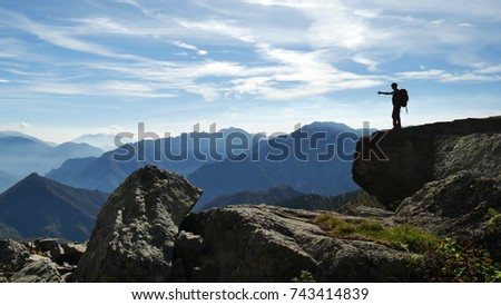 OROBIE MOUNTAINS, ITALY - CIRCA JUNE 2018: a hiker stands on a big boulder in the Orobie mountains and admires the beauty of  nature. #743414839