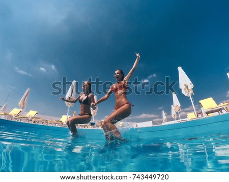 Summer fun. Two attractive young women in bikini jumping in the pool together #743449720