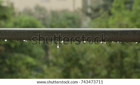 Raindrops on a handrail against a blurred background of green trees. Close-up shot. #743473711