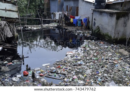 DHAKA, BANGLADESH - OCTOBER 28, 2017: A canal full with wastage plastic materials and toxic dyeing chemical in Narayanganj, near Dhaka, Bangladesh on October 28, 2017. #743479762