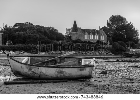 Small boat gounded in low tide in from of an manor #743488846