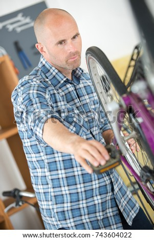 bicycle mechanic with wrench changing wheel on bike in workshop #743604022