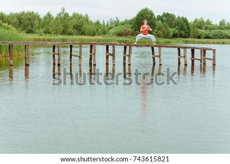 A man doing yoga on wooden pier at the lake #743615821