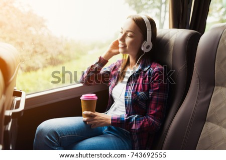 The woman on the passenger seat of the bus listens to music and drinks coffee. She looks out the window and smiles. Outside the window is a beautiful green landscape. #743692555