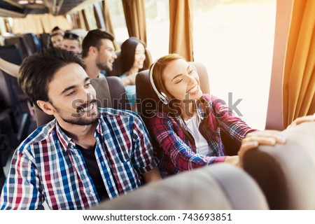 The guy and the girl are on the bus. The girl has headphones. He and the guy are discussing something and smiling. Behind them sit other tourists who are looking out the window to the sights. #743693851