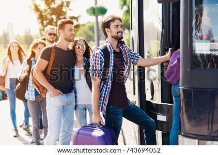 A group of tourists preparing to get on the bus. The guy with the girl goes into the bus and brings in their luggage. The girl goes first. Behind them is a group of tourists who are waiting. #743694052