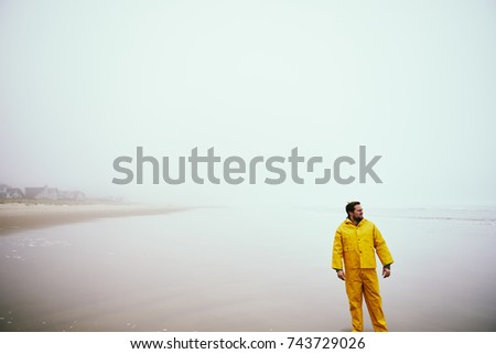 fisherman on beach looking out to ocean #743729026