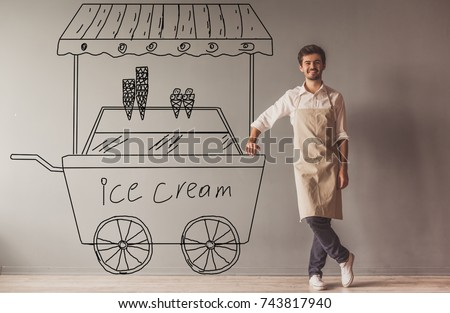 Handsome young guy in apron is leaning on drawn ice cream cart, looking at camera and smiling while standing at the wall