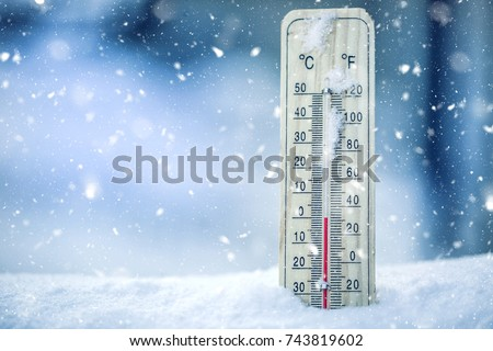 Thermometer on snow shows low temperatures in celsius or farenheit. #743819602