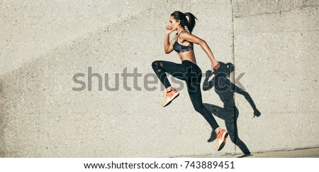 Fit woman exercising outdoors. Healthy young female athlete doing fitness workout. Royalty-Free Stock Photo #743889451