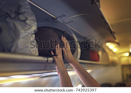 Passengers putting luggage into overhead locker on airplane. Hand putting luggage into panel overhead locker in airplane.  #743925397