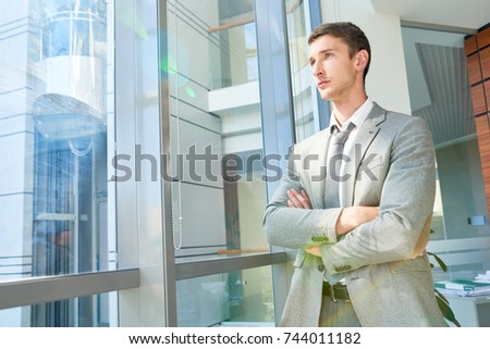 Portrait of confident young businessman standing by window with arms crossed looking away pensively, copy space #744011182
