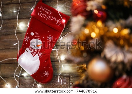 Christmas background with Red sock and christmas tree with christmas light