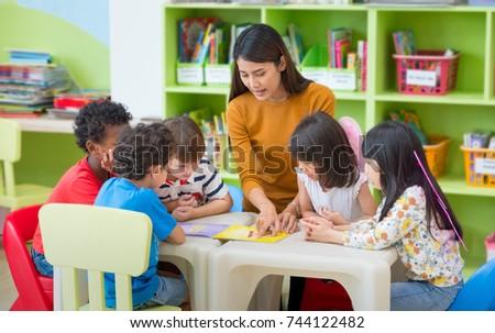 Asian female teacher teaching mixed race kids reading book in classroom,Kindergarten pre school concept Royalty-Free Stock Photo #744122482