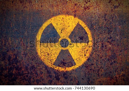 Radioactive (ionizing radiation) round yellow and black danger symbol painted on a massive rusty metal wall with dark rustic grunge texture background. Nuclear, radioactive alert concept. #744130690