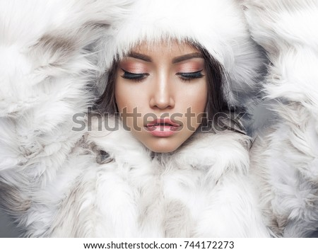 Fashion studio portrait of beautiful lady in white fur coat and fur hat. Winter beauty in luxury. Fashion fur. Beautiful woman in luxury fur coat. Fashion model posing in eco-fur coat and eco-fur hat #744172273