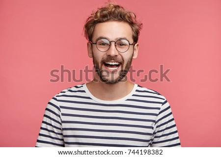Cheerful hipster guy smiles happily, has excited expression, dresssed casually, celebrates his anniversary or promotion at work, isolated over pink studio background. People, youth, emotions concept Royalty-Free Stock Photo #744198382