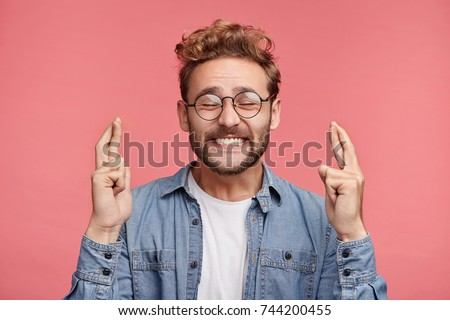 Glad positive bearded man crosses fingers, closes eyes with pleasure, anticipate hearing good news, isolated pink background. Happy male rejoices that his dreams came true. Excitement concept #744200455