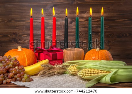 Kwanzaa festival concept with seven candles red, black and green, gift box, pumpkins, ears of wheat, grapes, corns, banana, bowl and fruits on wooden background, close up