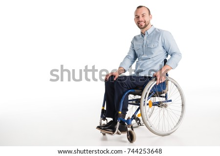 smiling disabled man in wheelchair looking at camera, isolated on white Royalty-Free Stock Photo #744253648