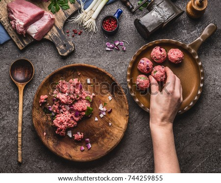 Female hand puts meat ball in frying pan. Preparation on kitchen table with meat, force meat , meat grinder and spoon, top view. Cooking,recipes and eating concept #744259855