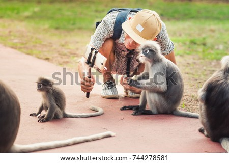 Travel selfie with funny monkeys. Young man takes a picture of wild animals. Spectacled langurs leave their isolated rocky forest to visit people to get food in Prachuap Khiri Khan, Thailand