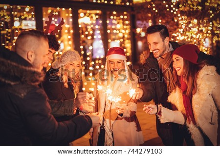 Group of a young friends in New Year eve with spark sticks have fun in the city street in front bright shop window.  #744279103