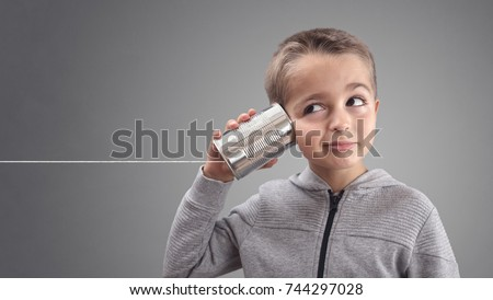 Boy on tin can phone listening to curious good news #744297028