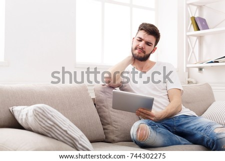 Sad young man at home with digital tablet, having neckache, sitting on couch at home, copy space #744302275