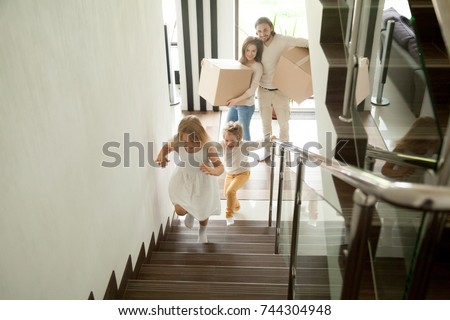 Happy children going upstairs inside two story big house, excited kids having fun stepping walking up stairs running to their rooms while parents holding boxes, family moving in relocating new home  #744304948