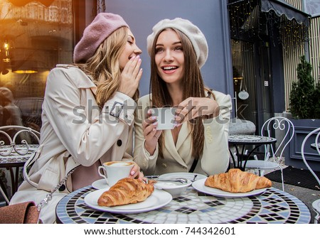Gossips with best friend. Horizontal shot of beautiful woman whispering to her friend's ear while drinking coffee in french vintage cafe. Women friends gossiping during coffee time. French style women #744342601