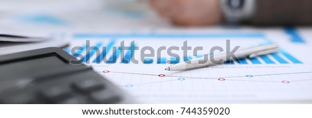 Financial statistics documents ball pen infographics at office table closeup. Internal Revenue Service inspector sum check investigation exchange market earnings savings loan and credit concept #744359020