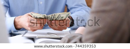 The businessman considers cash dollars in the office issues salaries to employees with black cash divides the profits as a result of illegal transactions everyone is happy. Royalty-Free Stock Photo #744359353