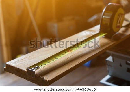 tape measurer on a wooden board close up #744368656