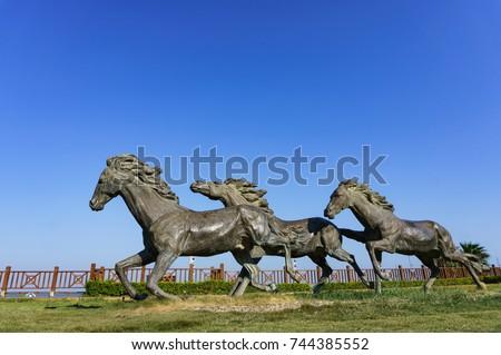 Xiamen, China - Oct 22, 2017: Running Horses Statue in Xiamen Guanyinshan Beach #744385552