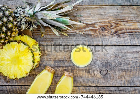 Tropical fruits juice. Bottle with beverage near pineapples slices on wooden background top view copyspace #744446185