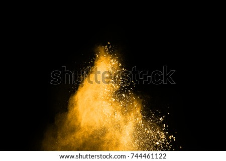 Abstract orange powder splatted background,Freeze motion of color powder exploding/throwing color powder,color glitter texture on black background. #744461122