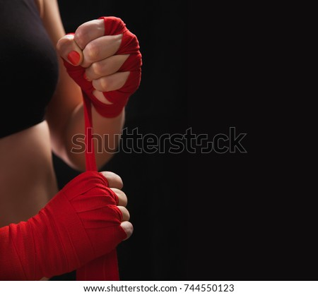 Female boxer is wrapping hands with red boxing wraps. Isolated on black background with copy space. Strong hand and ready for fight, active exercise and sparring. Close up. Women self defense. Royalty-Free Stock Photo #744550123