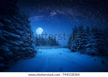 Full moon rising above the winter forest covered with fresh snow. Fantastic bright milky way in a starry sky. Christmas night.