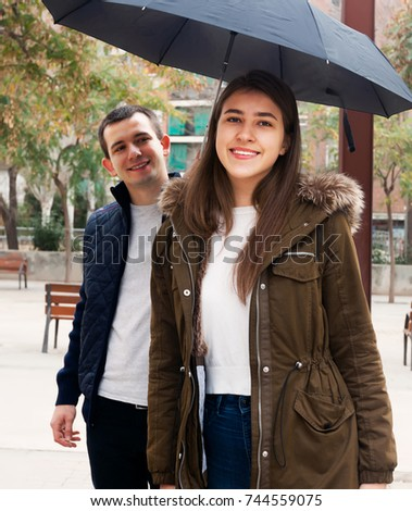 Young couple walking under umbrella at autumn day #744559075