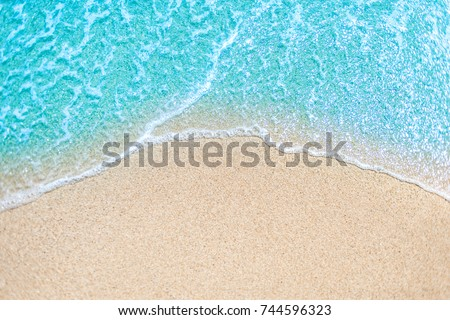Sea Beach and Soft wave of blue ocean.  Summer day and sandy beach background concept.  Royalty-Free Stock Photo #744596323