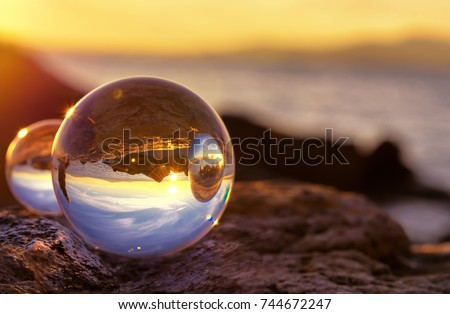 Crystal Ball Reflection on the seashore in sunrise light. Mirror reflections in two crystal balls