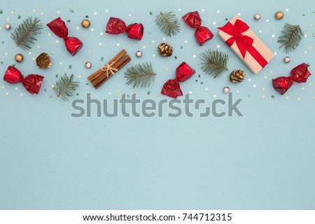 Christmas colorful pattern. New Year decorations on blue background. Gift box, candies, spruce, cones and gold confetti.  Minimal, flat lay #744712315