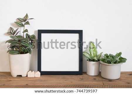 Mock up frame poster with tropical leaf plant in pot on wooden table. Lifestyle home decor