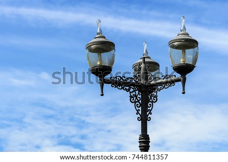 vintage lighting pole with twin double lamp lantern on background of blue sky. #744811357