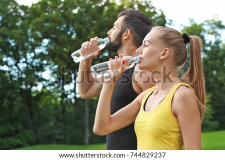 Young sporty couple drinking water in green park Royalty-Free Stock Photo #744829237