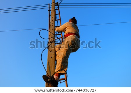 Electricians are climbing electricity poles. To install the electrical system #744838927