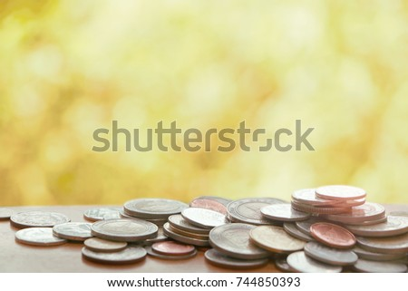 Many Thai coins on wooden table on bokeh yellow brown color tone background have flare light on coin #744850393