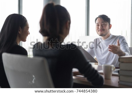 Smiling businessman during job interview.Job interview concept.Businessman explaining and listen to candidate answers. Setup studio shooting. #744854380