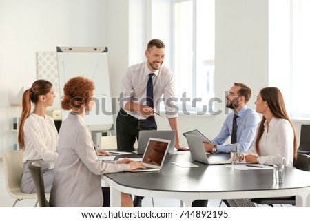 Team of young professionals conducting business meeting in office #744892195